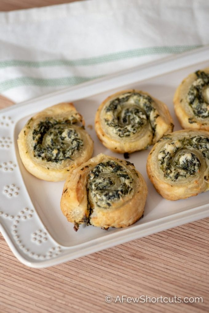 An insanely simple appetizer recipe that is sure to fly off of the plate! This easy Creamy Spinach Pinwheels Recipe is a winner! | @AFewShortcuts #appetizer #recipes #holidays #gameday #spinach
