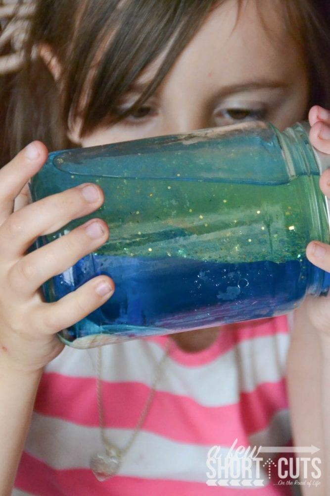 child looking at ocean jar