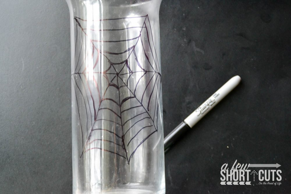 Spooky Halloween Decor for only a couple dollars! Check out this Simple DIY Spider Vase DIY craft project that will creep out all of your guests!