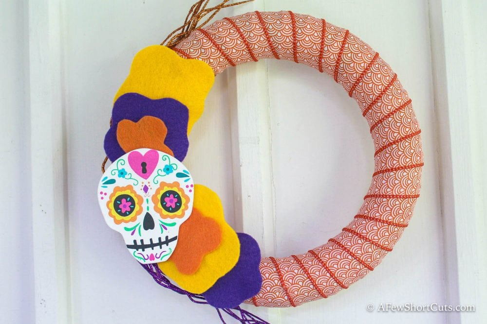 What a colorful way to kick off the halloween season. Look how simple this Dia de los Muertos DIY wreath is to make!