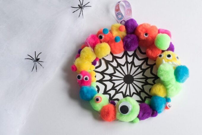 This halloween kids craft can't get much cuter! Find out just how simple it is to make this DIY Monster Wreath with your little monsters.