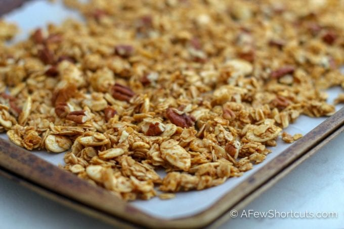 The warm spices of fall in a delicious granola blend. This Homemade Pumpkin Spice Granola Recipe is so easy to make and perfect sprinkled over a little bowl of yogurt or on its own. | @afewshortcuts #pumpkin #breakfast #granola #recipe #glutenfree #vegan #pumpkinspice
