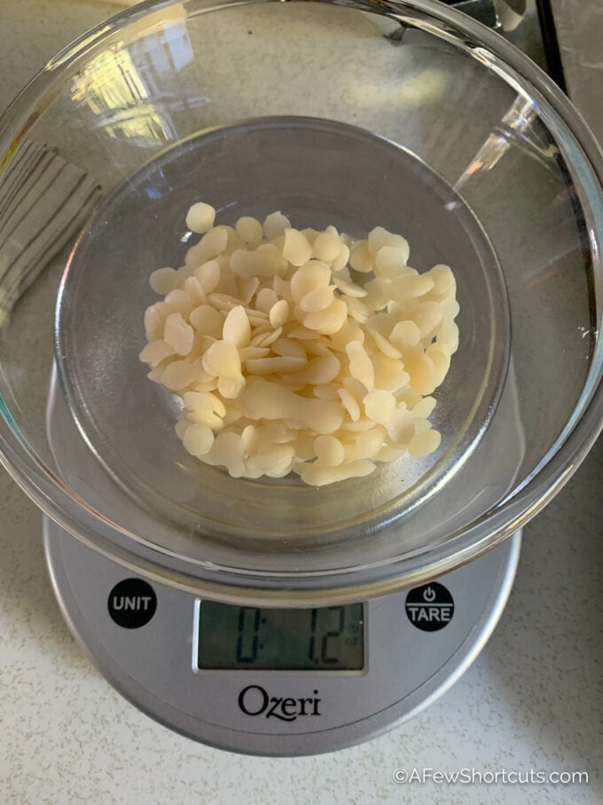 beeswax pellets in bowl on scale