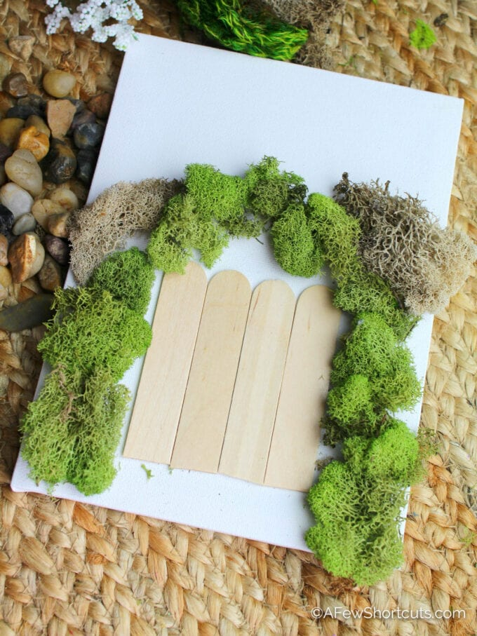 moss and popsicle sticks on canvas