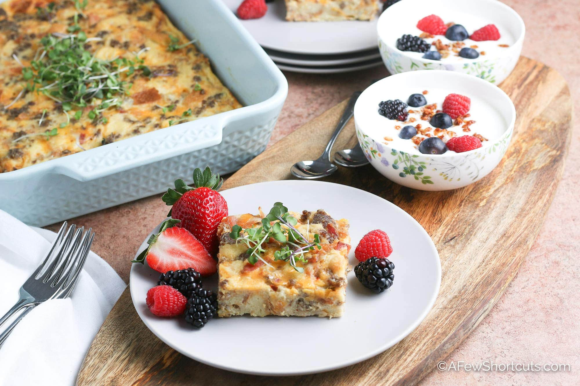 Overnight breakfast casserole on plate with fruit