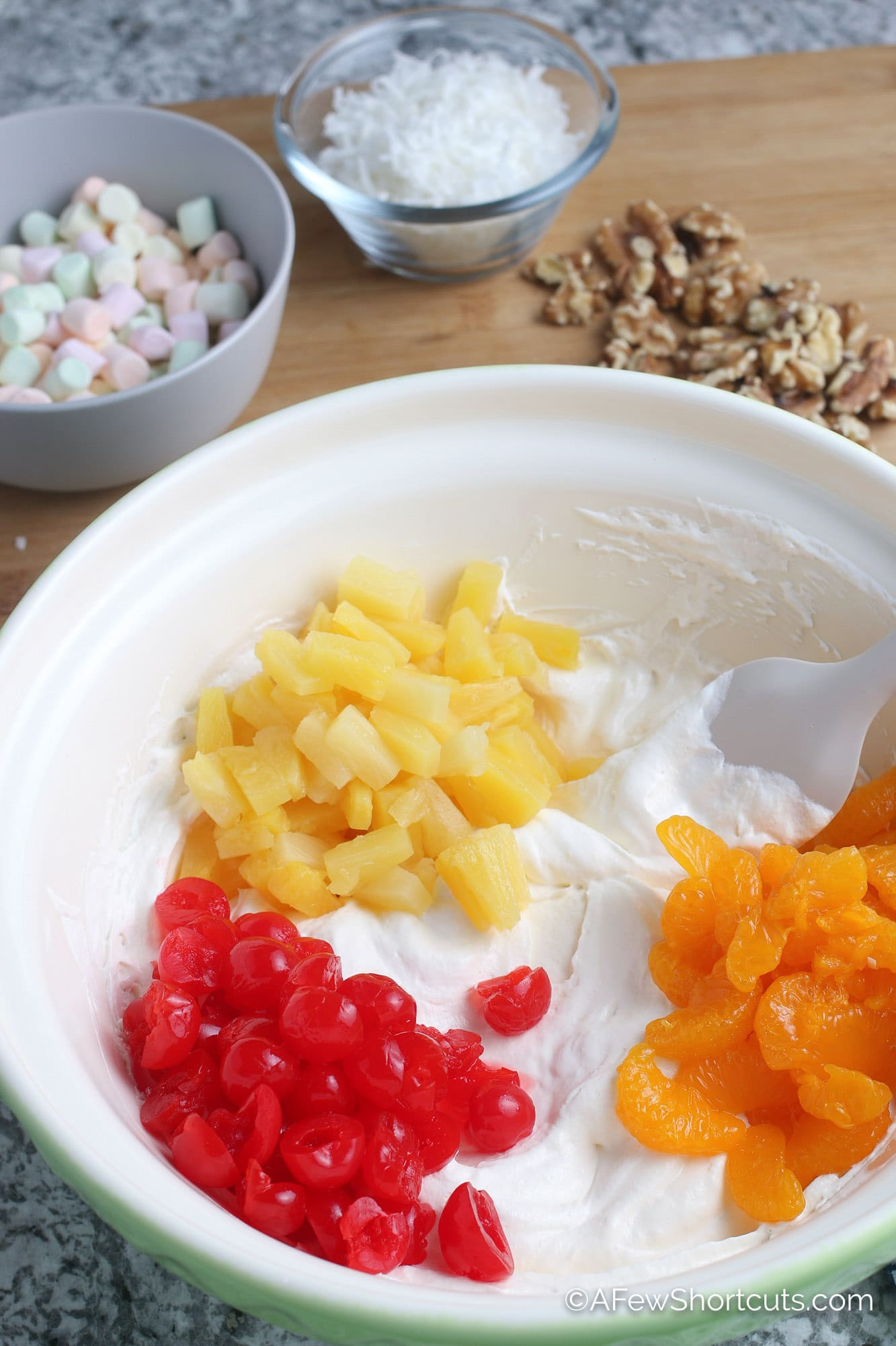 Fruit and whipped topping in bowl for ambrosia salad