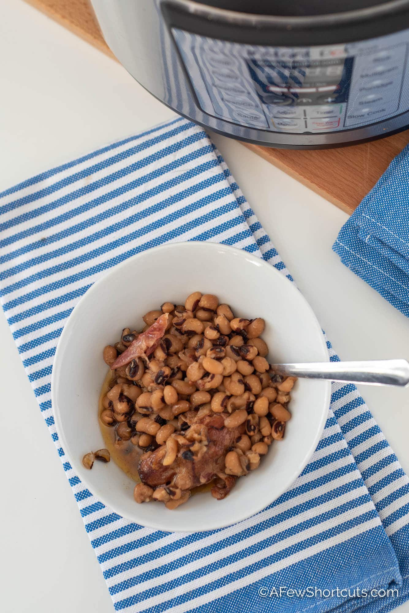 Black Eyed Peas in bowl with blue striped towel under it.