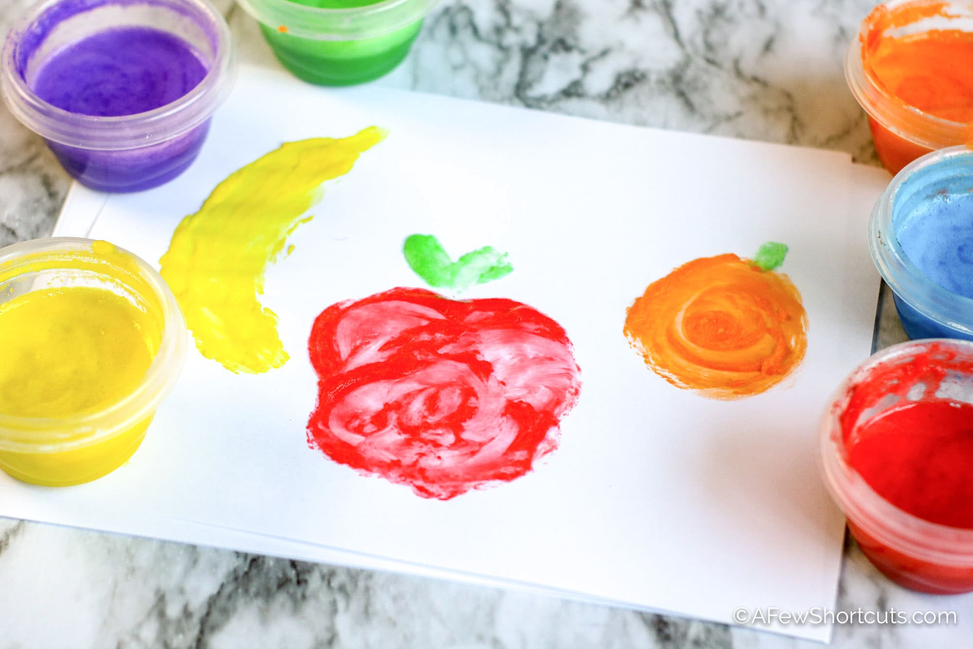 Fruit painted on white paper with homemade finger paint.