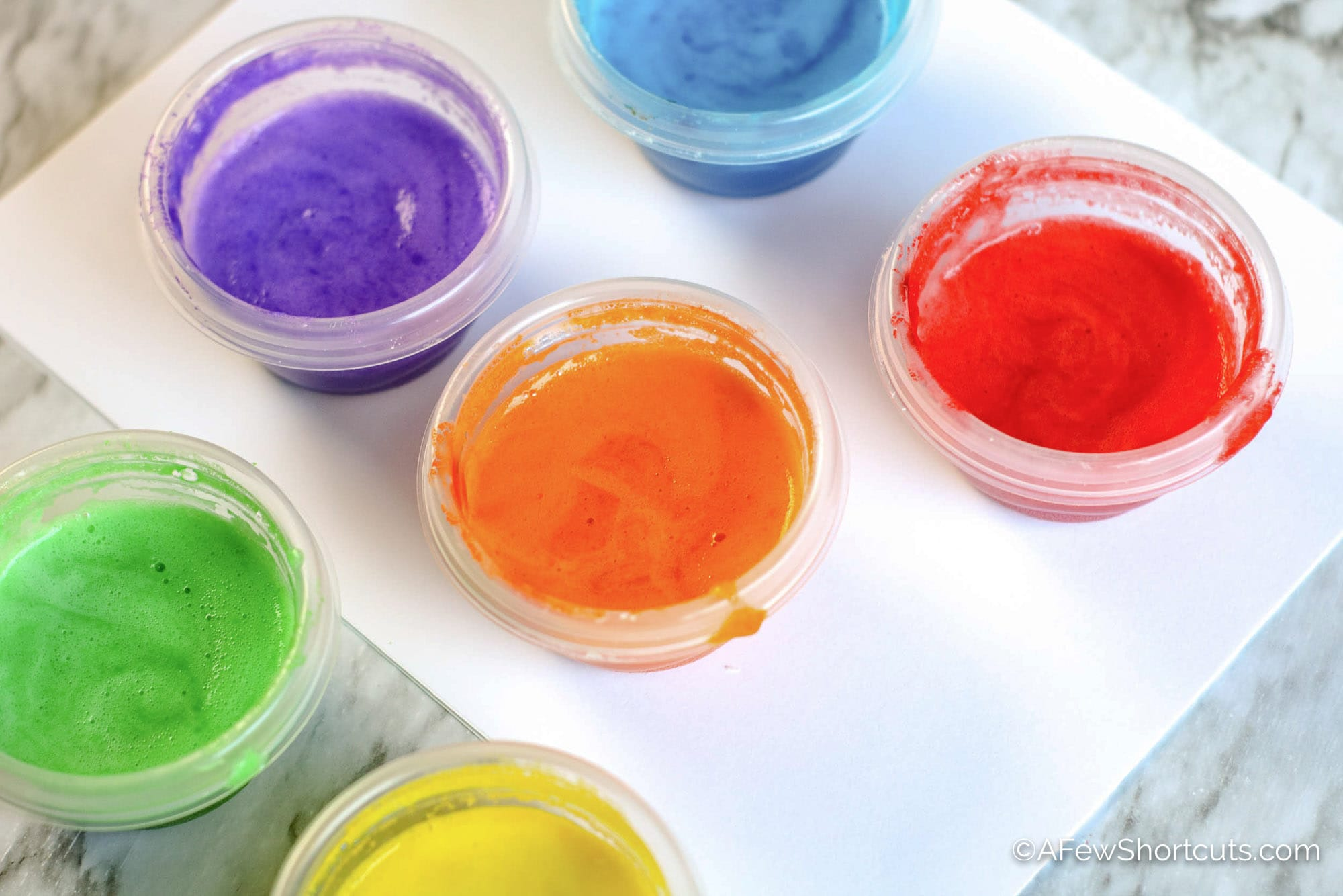 Homemade finger paint in cups with paper.