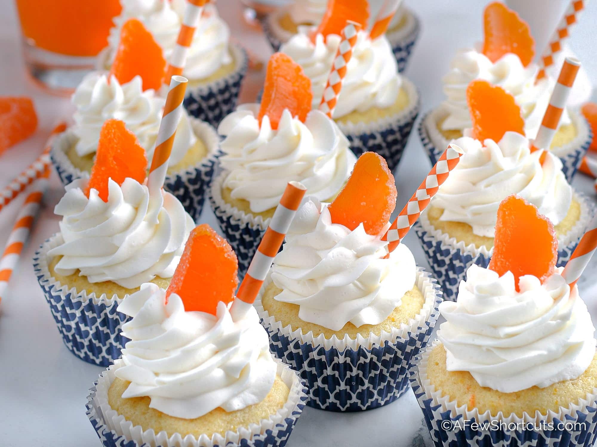 Orange Creamsicle Cupcakes With blue cupcake liner and orange straw
