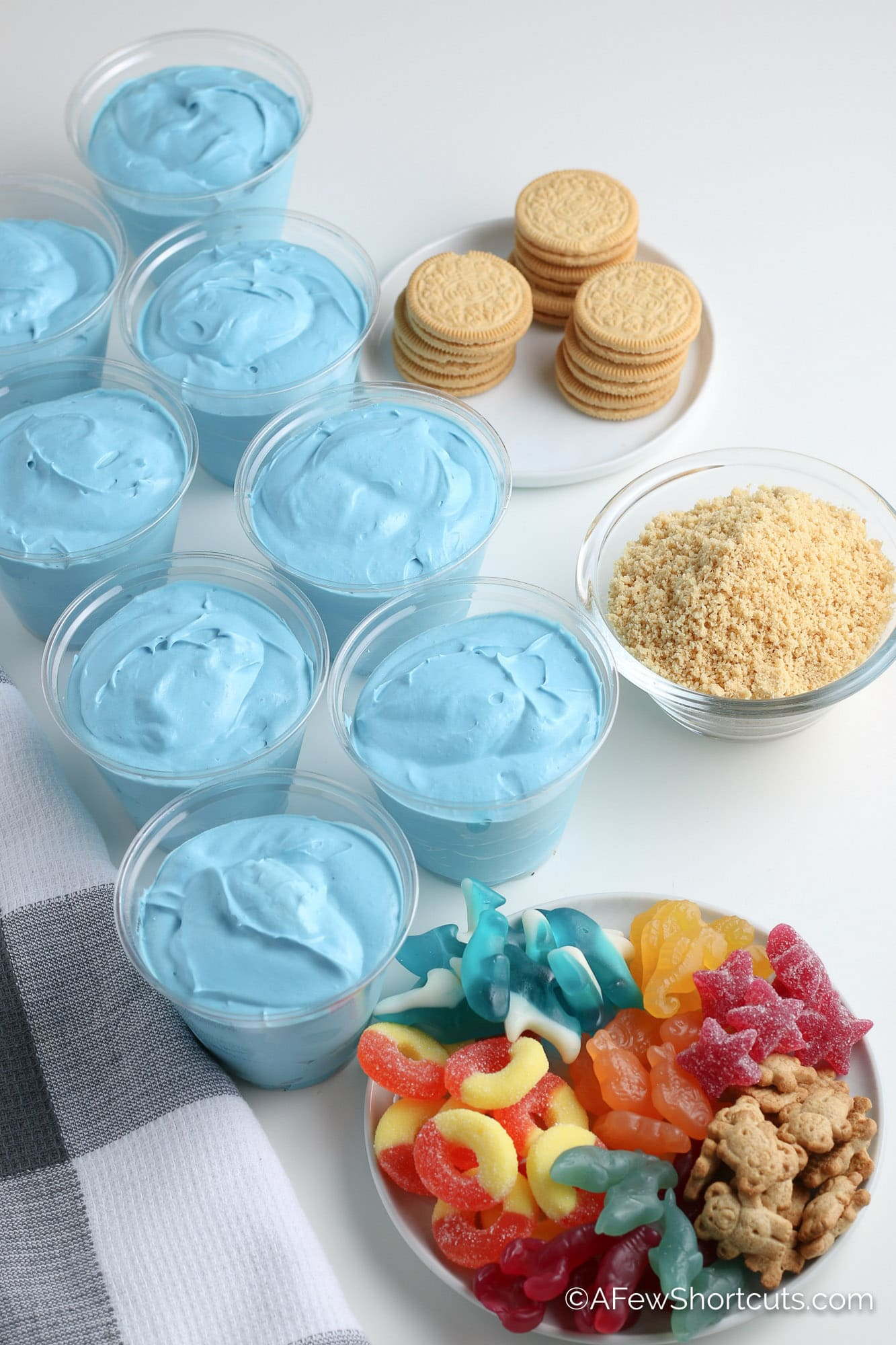 Blue pudding in dessert cups with plate of gummy candy and crushed vanilla cookies