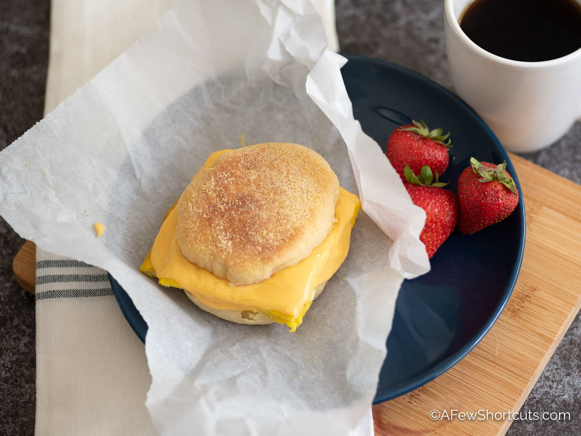 Breakfast Sandwich on plate with strawberries and coffee