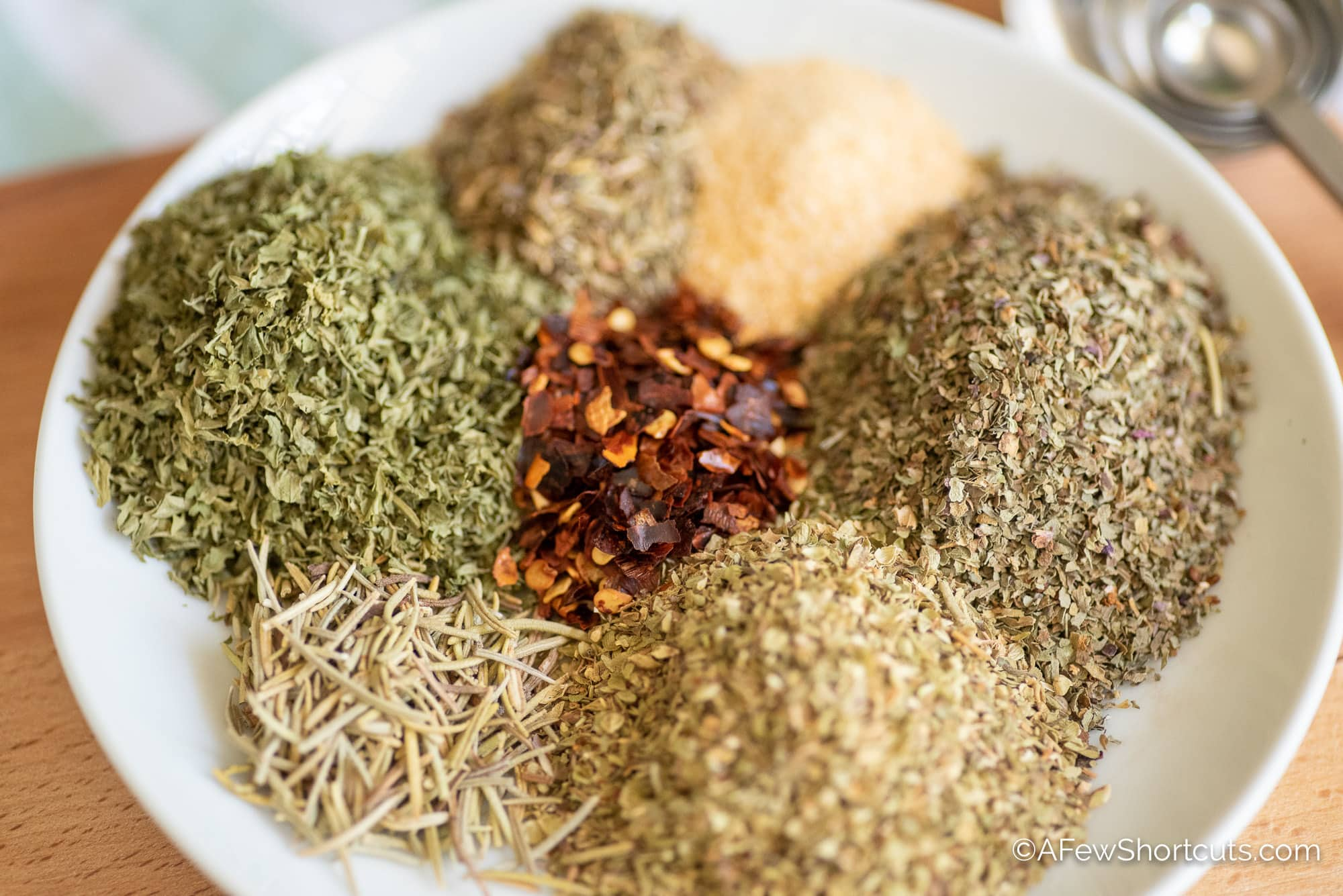 Spices for Italian seasoning on white plate.