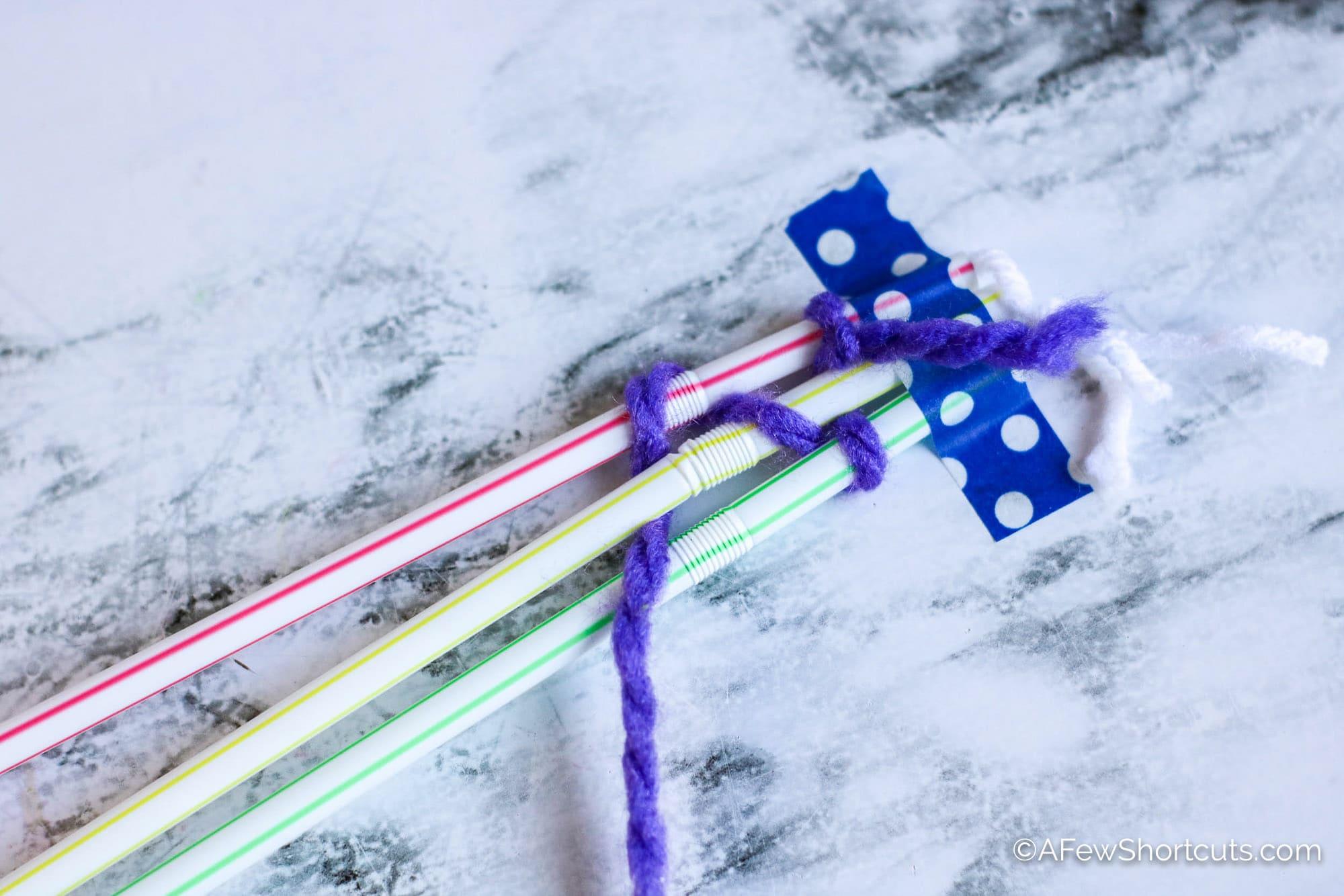 purple yarn woven around straws