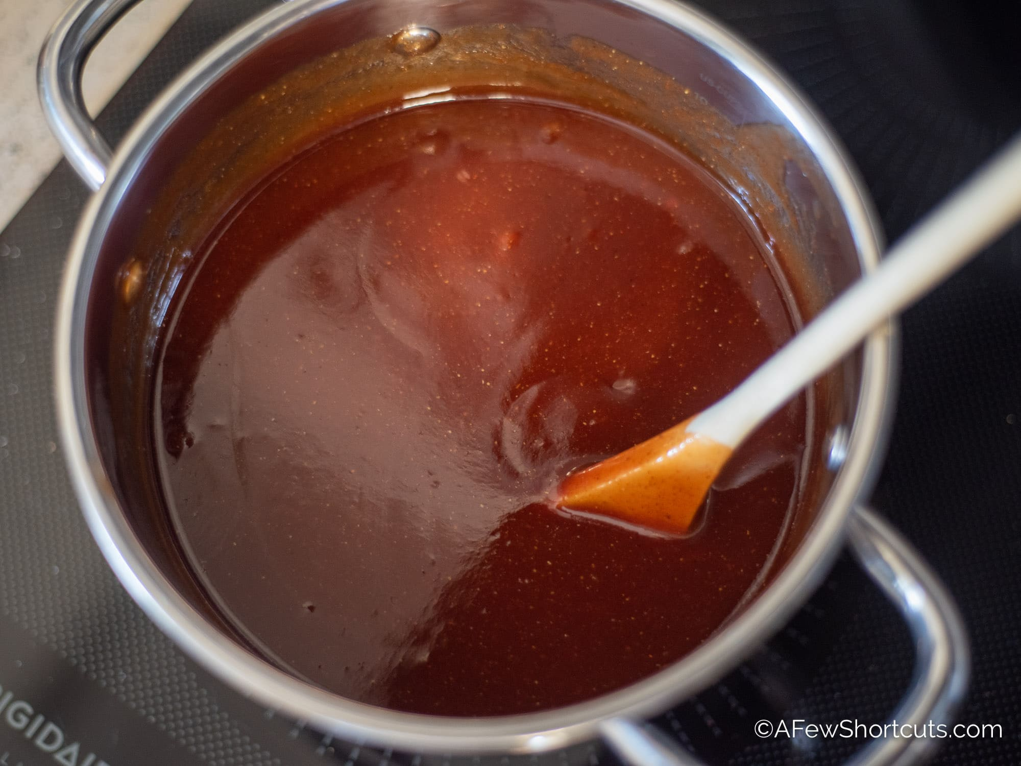 The Best Homemade Sweet BBQ Sauce in saucepan with wooden spoon